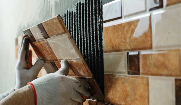 a tiler placing ceramic wall tile in position over adhesive